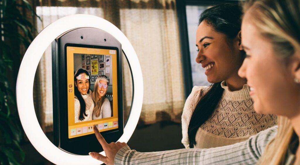 Två tjejer som leende använder en photo booth