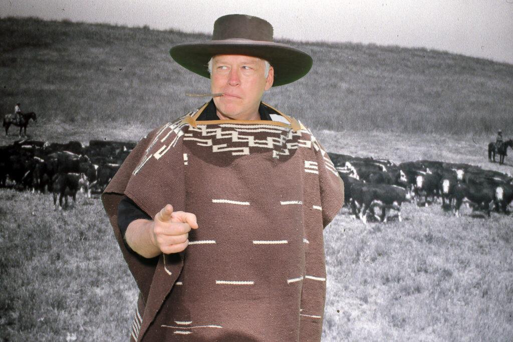 Man klädd som Clint Eastwood cowboy framför en svartvit bild av en massa kor.